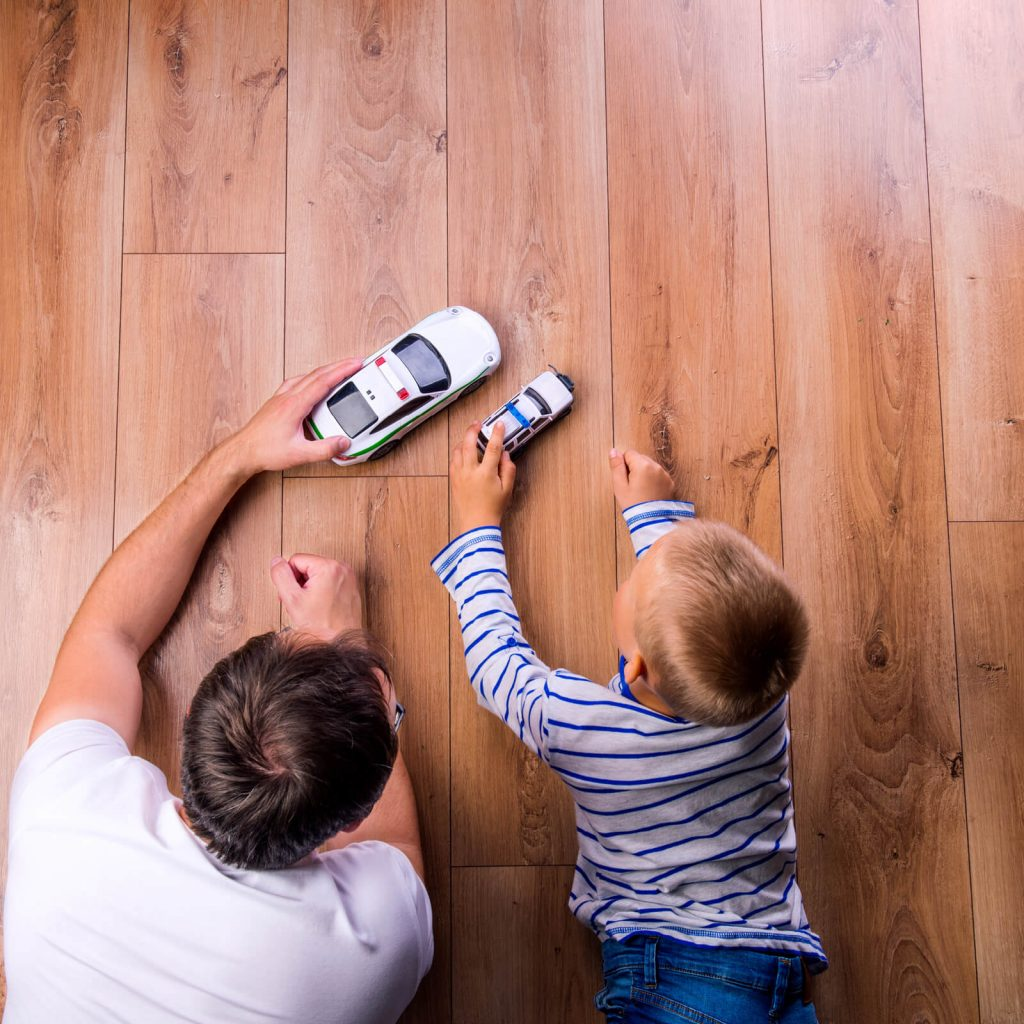 Kid and father playing on Hardwood floor | Design Waterville
